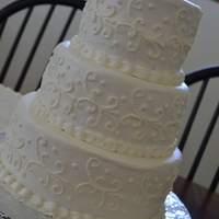 White On White Wedding Cake 3 tiered round wedding cake. White on white with scroll work. Matching sheet cake