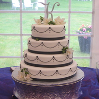 Beautiful White And Black Wedding Cake MMF with black royal icing details and real flowers.