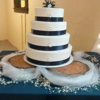 Winter Theme Cake Each teir is a different flavor cake with raspberry as the filling, decorated with buttercream frosting, ribbon, and used a boutineer as a...