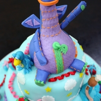 "Dibo The Gift Dragon And Friends 5""+7"" 2 tier cake with gumpaste Dibo and friends hand moulded figurines."