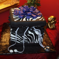 Zebra Gift Box For 50Th Birthday Celebration Square cake layers covered with fondant and zebra sugar sheets with purple fondant bow and black fondant tissue.