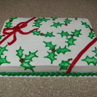 Christmas Gift Cake French Vanilla cake with BC icing and MMF ribbon. Used Brush Embroidery technique for holly leaves