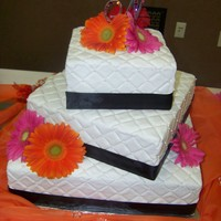 Gerber Daisy Quilt Cake All buttercream cake with black ribbon around the edge. Bride wanted fresh flowers on cake. Made it quilt like and place a little pearls...