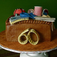 Sewing Basket Cake Marshmallow fondant covered wasc with buttercream. All items in basket are fondant with the exception of the spools of thread. Those are...