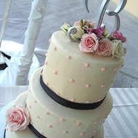 Black And Pink Buttercream with black ribbon, pink dots and pink live roses