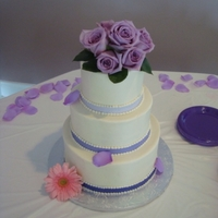 Purple Roses Wedding Buttercream with purple fondant ribbon. Live roses placed on top.