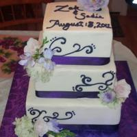 Purple Themed Cake With Fresh Flowers Bride Wanted Their Names And The Date On Top With Purple Scroll Work *Purple themed cake with fresh flowers. Bride wanted their names and the date on top with purple scroll work.