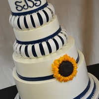 Arched Navy Blue And Sunflowers   Italian Buttercream cake with gumpaste arches and navy blue fondant accents. Gumpaste Sunflower