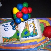 Oh The Places You'll Go 1St Birthday Cake  yellow cake book with buttercream pages, edible image edited to say birthday message and fit the cake book, cake pop balloons stacked on a...