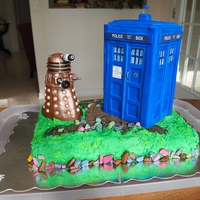Dr Who's Tardis And Dalek Chocolate fudge cake with buttercream icing decorated with the TARDIS and an enemy Dalek!