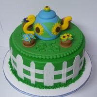 "Tea In The Garden   9"" rd with BC finish with fondant accents. Sunflower teapot and flowerpots also made of fondant. TFL!"