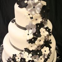 Black, White And Silver Flowers. Cake is covered in fondant with real ribbon and fondant/gumpaste mix flowers. The cool thing about this cake is that fact that I made it...