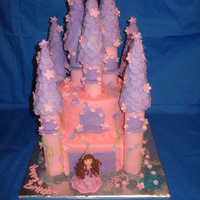 A Princess Castle Cake Towers made from fondant as well as the flowers and the little girl. The girl was made to look like the little girl, so that it was her...
