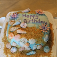 Beach Birthday   Covered with MMF, shells and flowers made from gumpaste.