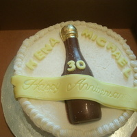 30Th Anniversary Cake   Pina Cola Cake with buttercream icing banner made of fondant bottle solid chocolate with gold top