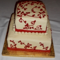 Square Wedding Cake With Red Accents Almond cake with Cream Cheese Icing. Fondant ribbon & buttercream piping. Had a hard time getting crisp corners with the CC icing, so...