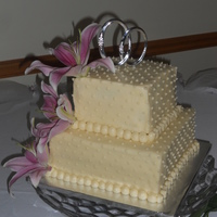 Cake With Buttercream Square cake with dots, made with buttercream, fresh stargazers on side