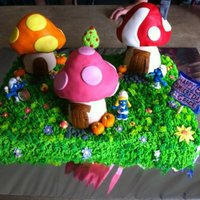 Smurf Village Cake buttercream grass, rice crispie houses, the rest of the decorations are MMF, the smurfs are plastic figurines