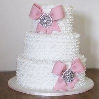 Frilly Bows Wedding Cake. This cake is inspired by a Maisie Fantasie design. Bride wanted big pink bows to tie into her wedding. The frills are all done with...