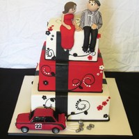 Handpainted, Red, Black, White Wedding Cake. Topper is made of icing. Drag car is carved from styro then decorated with fondant. Deco on the cake is handpainted, then fondant flowers....