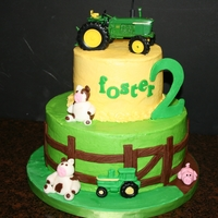 "Foster's John Deere Vanilla cake 10"" and 6"", buttercream with fondant accents. Toy tractor on top."