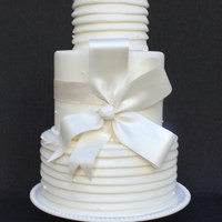 Blanc.  This 3 tier wedding cake is a classic couture, white on white design. The bottom and top tier are covered in fondant pleats, while the tall...
