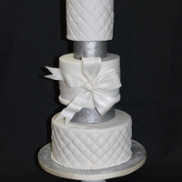 Silver & Couture This three tier wedding cake was for a small gathering. A couture bow and flower sit on a quilted cake with silver separators.