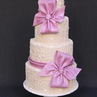 Spiderweb Lace And Light Plum Bows  This 4 tier wedding cake has a piped spider web lace design in a champagne hue. I decided to make plum colored bows since plum is one of...
