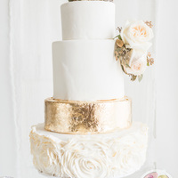 Gold Leaf Wedding Cake Edible gold leaf wedding cake with fondant ruffle roses. Ruffle roses are bushed with gold as well.