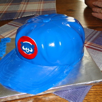 Cubs Baseball Cap Cake This was a very last minute cake. It was yellow cake with BC and MMF. The cubs logo was edible image on gumpaste plaque. This was carved...