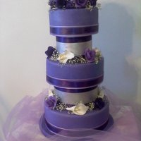 Midnight Love Dark purple cake with alternating smaller silver tiers. Gumpaste roses, lilies, and freesia.