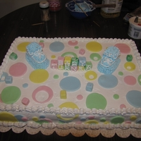 Poka Dot Cake basic butter cream Icing with fondant accent. Booties made out of stacked Twinkies.