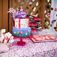Alice In Wonderland Dessert Table Cake, purple chocolate fountain with marshmallow and fruit dippers, cookies, chocolate dipped pretzels, cupcakes, and mini cupcakes