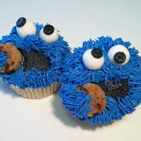 Cookie Monster Cupcakes Black and blue BC, fondant googly eyes. For the cookie I used a cutter to trim up a mini Famous Amos cookie.