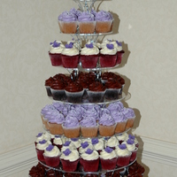 "Wedding Cupcake Tower - Purple Gumpaste Flowers This was 144 cupcakes. 6"" cake on top iced with purple cream cheese icing and gumpaste floral bouquet on top."
