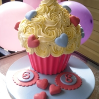 Wilton Giant Cupcake.  Birthday cake for both of my daughters to share. (One day apart) I BIG thank you to mrsvb78 for the tutorial on the chocolate wrapper. No...