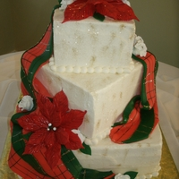 Blissful Christmas Wedding Kake 3 tier square wedding with poinsetta accents and a tartan drape