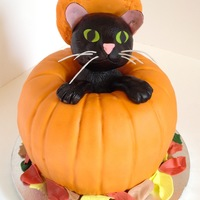 Pumpkin Halloween Cake With Black Cat Pumpkin Halloween cake with a black cat peeking out.