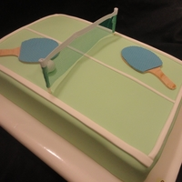 Ping Pong Cake  2 stacked 9 x13 cakes covered in green fondant and detailed in white. The net is not edible but the paddles are - they are made of gumpaste...