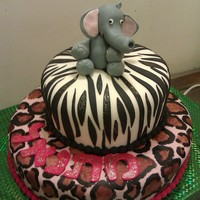 Animal-Themed Birthday Cake  Two tier cake. Bottom tier decorated in leopard print. Top tier decorated in zebra print. Adorned with a gumpaste elephant on top. Elephant...