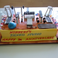 1St Anniversary Of A Gym its a chocolate cake , covered with fondant & the equipment is of gumpaste
