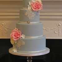 Roses And Lace Pretty blue cake with pink and ivory flowers, finished with lace detail