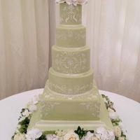 Green Stencilled Cake Stencilled wedding cake with roses, freesias and hydrangea
