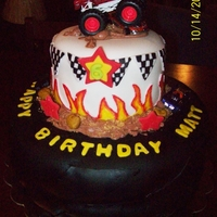 Monster Truck  This is a monster truck cake with bottom tier shaped like a monster truck tire with dirt and cars on it and top tier has the flags with the...