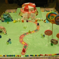 Candyland Cake Two tier cake top layer peppermint bottom tier candy buttons. THe gameboard has a rice crispy and poured sugar waterfall , cotton candy...