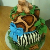 Safari Themed Babyshower Cake   The baby giraffe is RKT covered in fondant and hand painted. Cake is covered in MM fondant with handpainted animal print and fondant bow