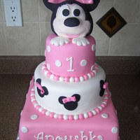 "Minnie Mouse First Birthday 10"" square, 8"" & 5"" rounds covered & decorated in fondant. Minnie head is RKT covered in fondant."