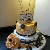 A Music Themed Cake Two tier chocolate fudge cake with the chocolate ganache covering under the fondant...I sprayed the top tier in gold but dusted the peony...