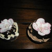 Cupcakes With Fantasy Flowers Chocolate cupcakes with fantasy flowers made of gum paste and dusted with pink powdered color on the edges. I put buttercream on half of...