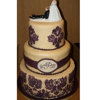 Purple And Ivory Damask Purple and ivory damask wedding cake with hand piped monogram. Fondant with royal icing stencilling. Top tier is vanilla with lemon filling...